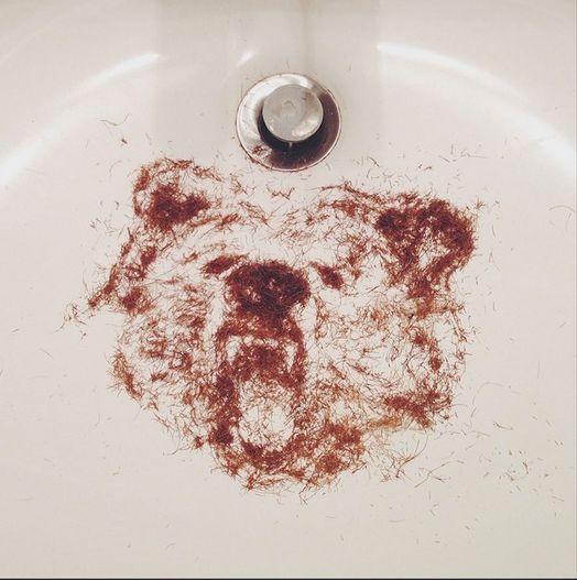 Photo représentant une figure d'ours réalisée avec des poils de barbe dans un lavabo avant usage du bavoir à barbe