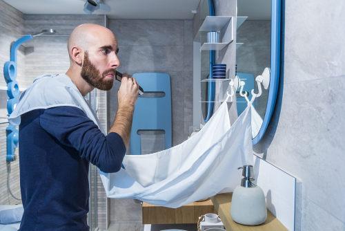Photo représentant un homme se taillant la barbe avec attaché à son cou un bavoir à barbe Les Boomeurs
