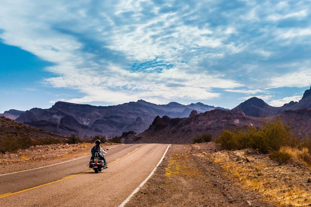 Photo d'une route déserte en Californie avec un motard qui roule seul, parue dans les Boomeurs