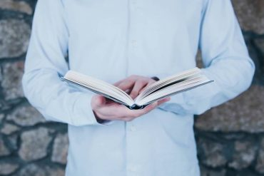homme debout lisant un livre